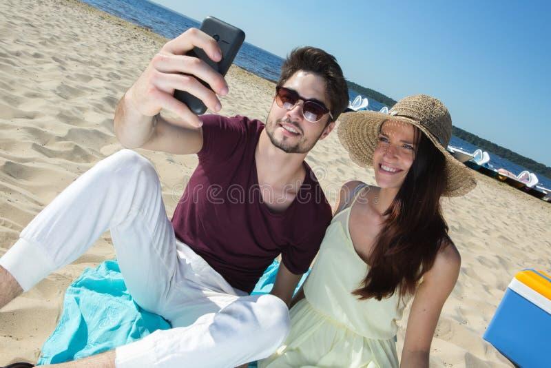 坐在海滩和做selfie的华美的年轻夫妇 免版税库存照片