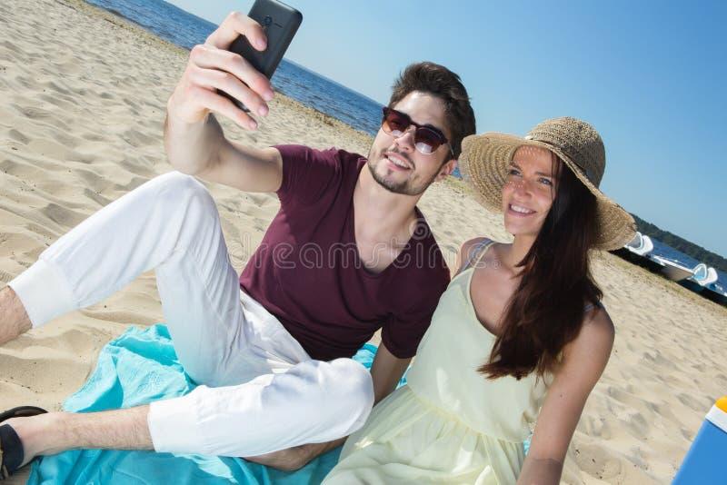 坐在海滩和做selfie的华美的年轻夫妇 免版税库存图片