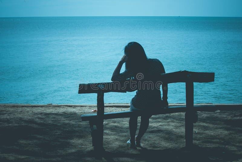 坐在海滩的长木凳和看对蓝色海的孤独的妇女剪影 免版税图库摄影