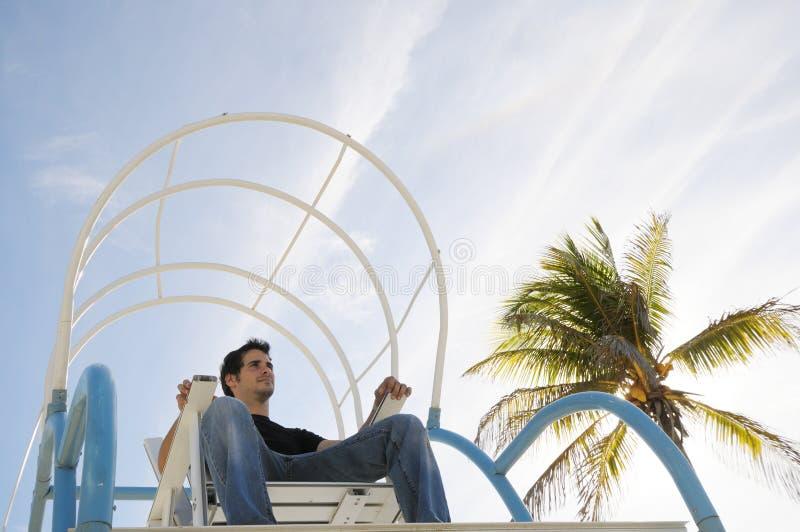 坐在海滩睡椅的男孩 免版税库存照片