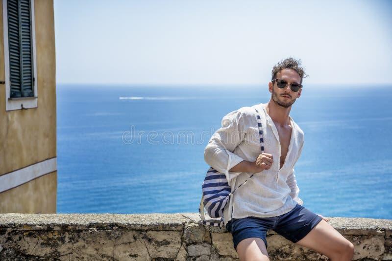 坐在海边镇的英俊的人 免版税库存照片