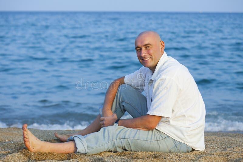 坐在海附近的人 免版税库存照片