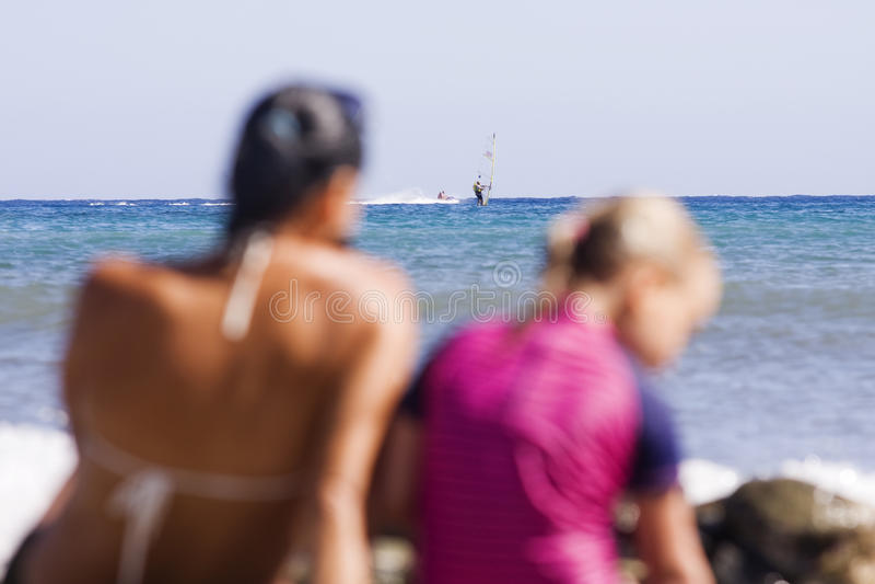 坐在海滩和享受他们的假日的年轻家庭 图库摄影