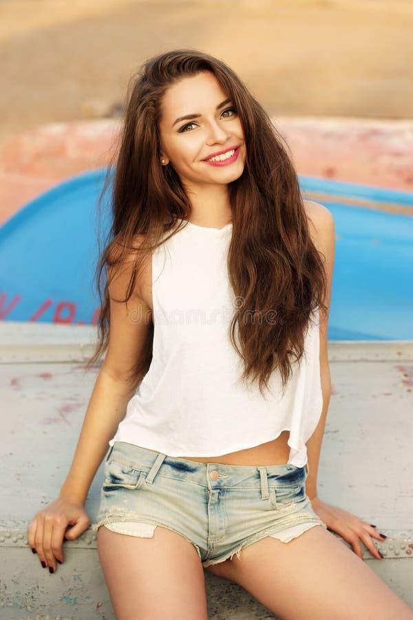 坐在海滩的愉快的微笑的女孩 库存照片