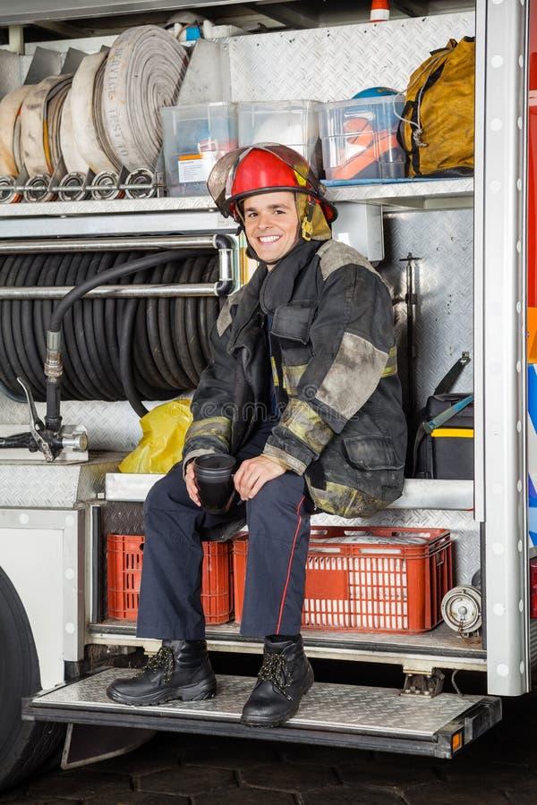 坐在消防队的愉快的工作者 免版税库存照片