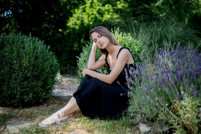 坐在淡紫色花附近的黑暗的礼服的年轻女人 免版税图库摄影