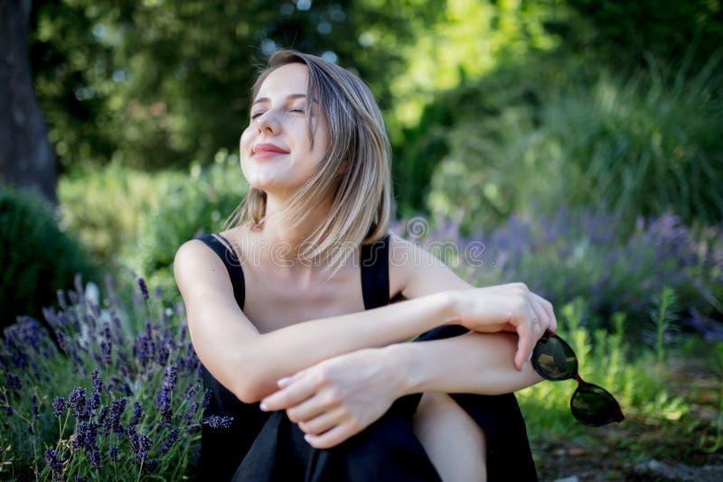 坐在淡紫色花附近的黑暗的礼服的年轻女人 免版税库存图片