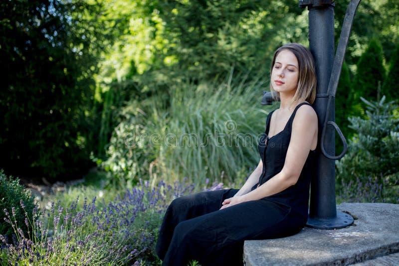 坐在淡紫色花附近的黑暗的礼服的年轻女人 免版税库存照片