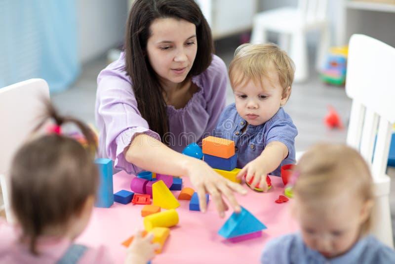 坐在游戏室的桌上的女老师与三幼儿园儿童修建 库存图片