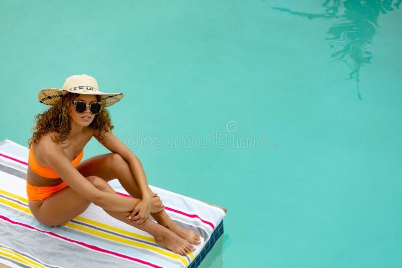 坐在游泳场边缘的太阳镜和帽子的妇女  免版税库存照片