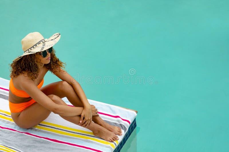 坐在游泳场边缘的比基尼泳装和帽子的妇女  图库摄影