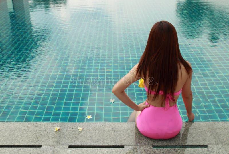 坐在游泳池的妇女 库存图片