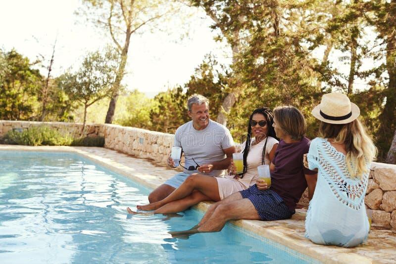 坐在游泳池谈话的边缘的两对夫妇 免版税图库摄影