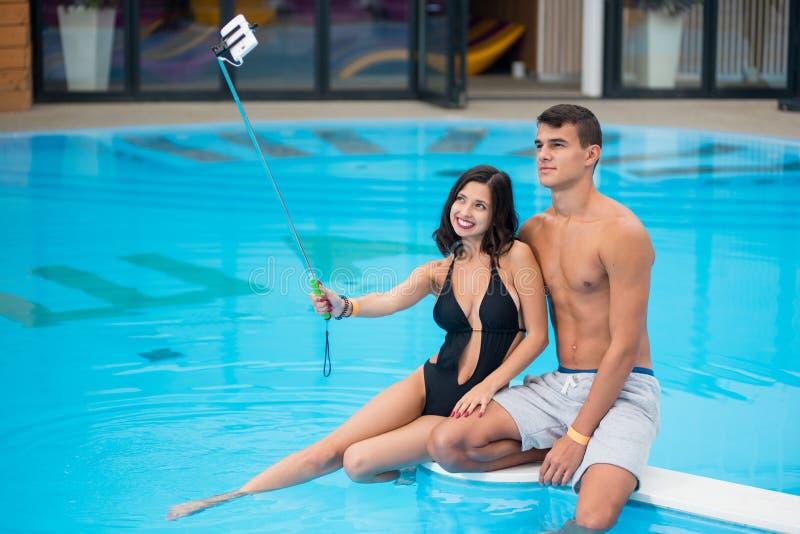 坐在游泳池边缘和拍selfie照片的年轻夫妇在电话用selfie棍子 免版税图库摄影