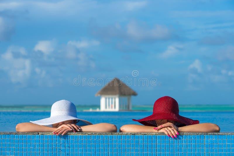 坐在游泳池边缘的帽子的两名妇女 免版税库存图片