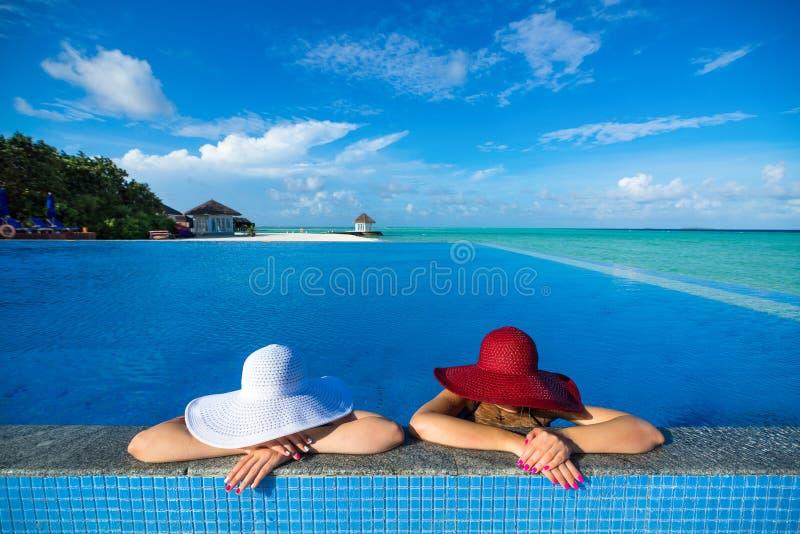 坐在游泳池边缘的帽子的两名妇女 免版税库存照片