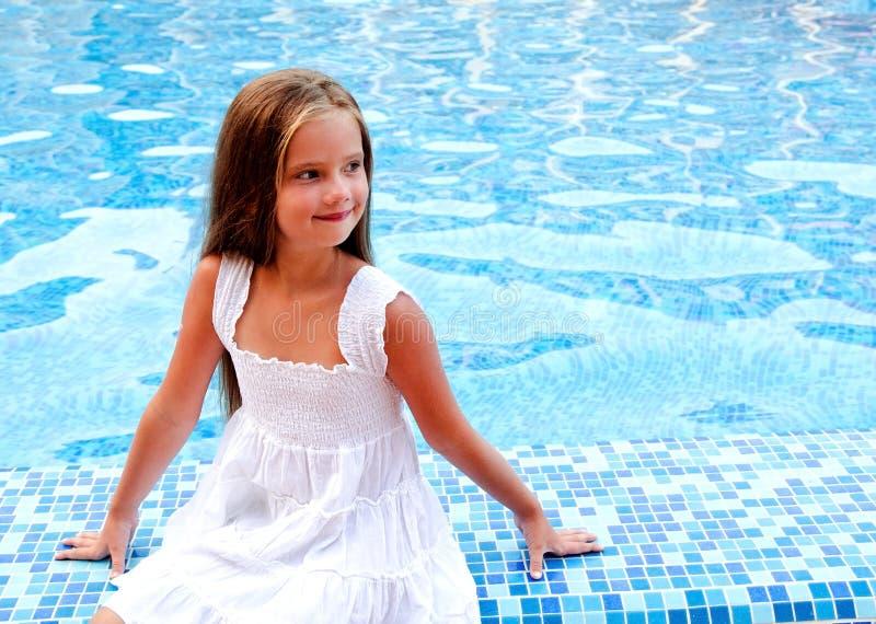 坐在游泳池附近的可爱的微笑的小女孩 库存图片