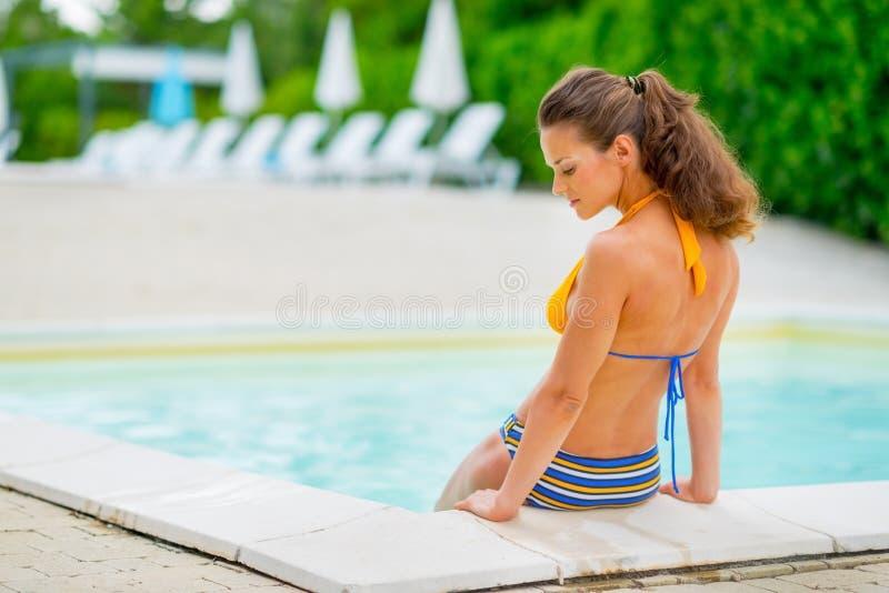 坐在游泳池附近的少妇 库存图片