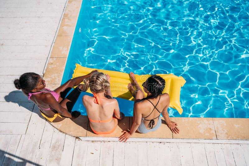 坐在游泳池附近的年轻美丽的不同种族的妇女 免版税库存照片