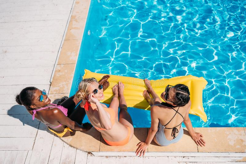 坐在游泳池附近的年轻美丽的不同种族的妇女 库存图片