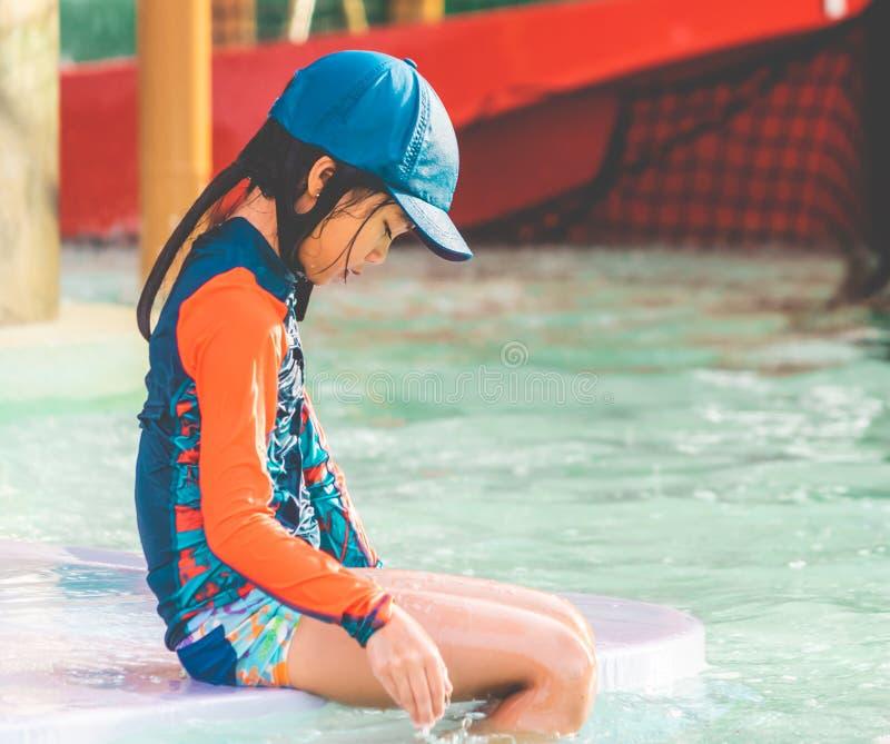 坐在游泳的训练水池的疲乏的女孩 免版税库存图片