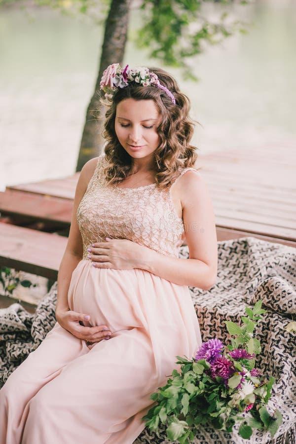 坐在湖附近的年轻人孕妇 库存图片