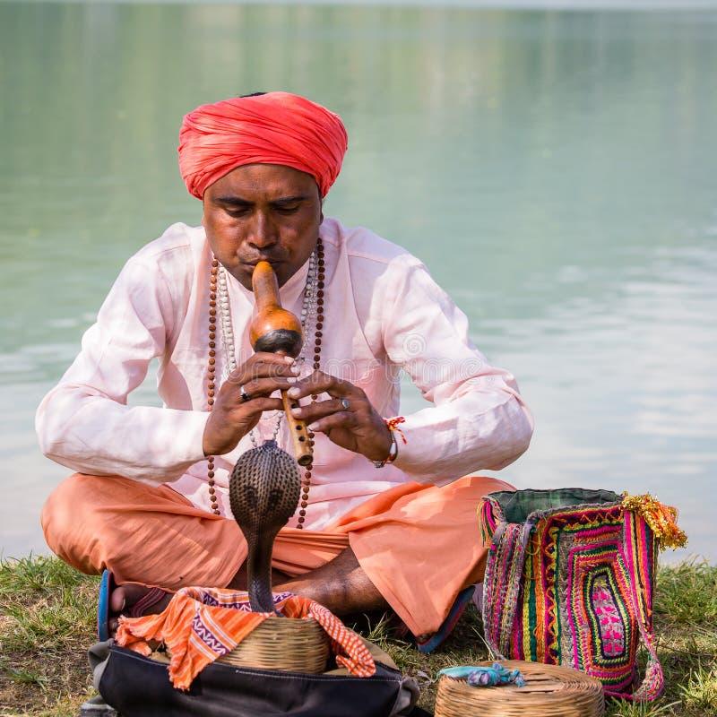 坐在湖附近的头巾和眼镜蛇的画象耍蛇者成人人 尼泊尔pokhara 库存图片