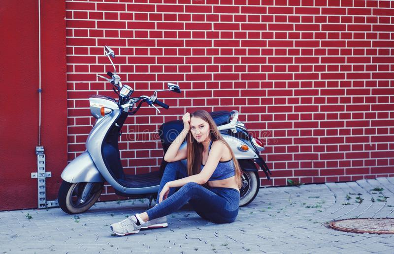 坐在滑行车摩托车附近的妇女 免版税库存图片