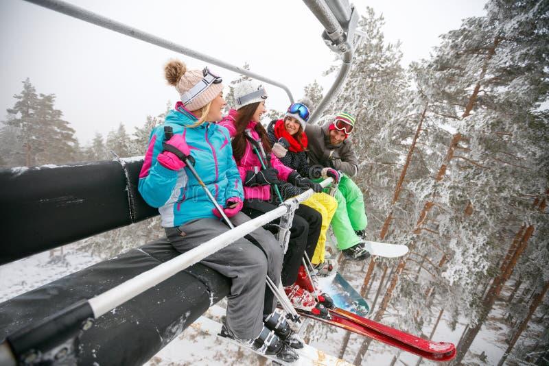 坐在滑雪升降椅的朋友滑雪者在美好的晴天 库存照片