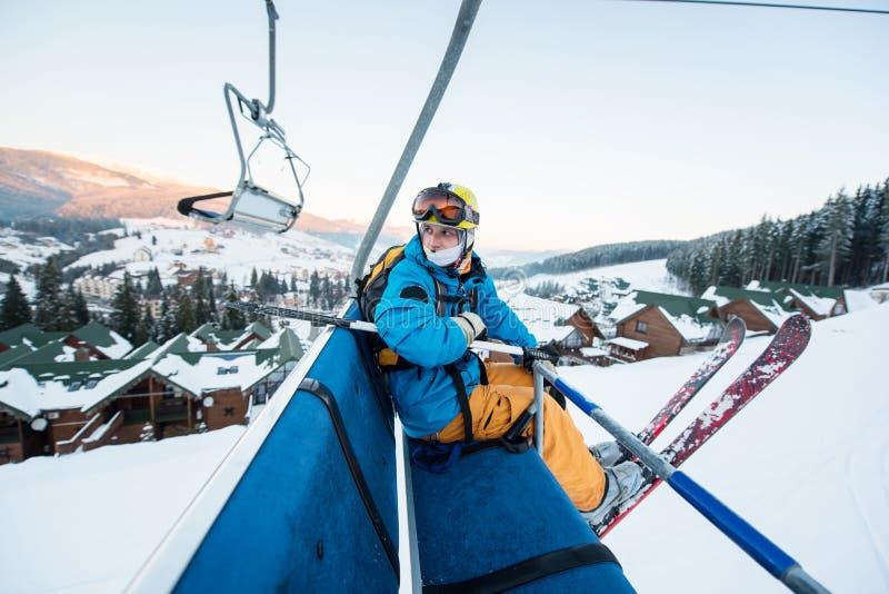 坐在滑雪升降椅的滑雪者人在美好的天和转回去 特写镜头 滑雪的概念 免版税库存图片