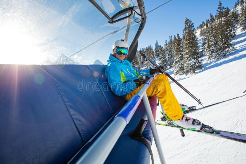 坐在滑雪升降椅的滑雪者 免版税库存图片
