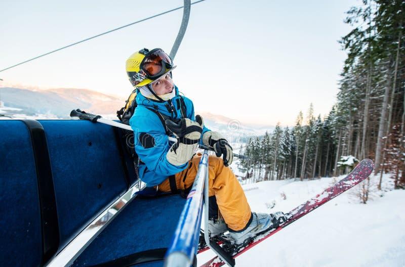 坐在滑雪升降椅的特写镜头滑雪者看照相机 库存照片