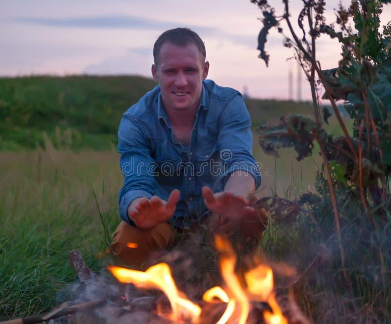 坐在火附近的人 库存图片