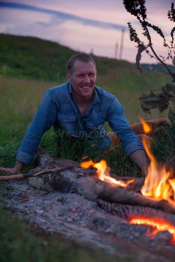 坐在火附近的人 免版税图库摄影