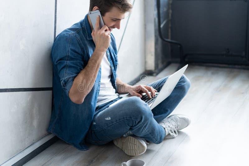 坐在灰色墙壁的年轻白种人人使用计算机膝上型计算机和智能手机 免版税库存图片