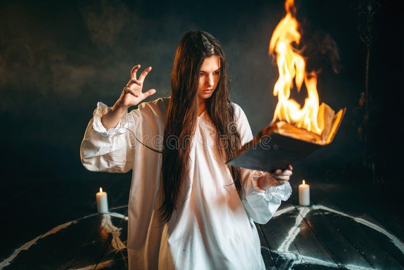 坐在灼烧的五角星形圈子,魔术的妇女 库存图片