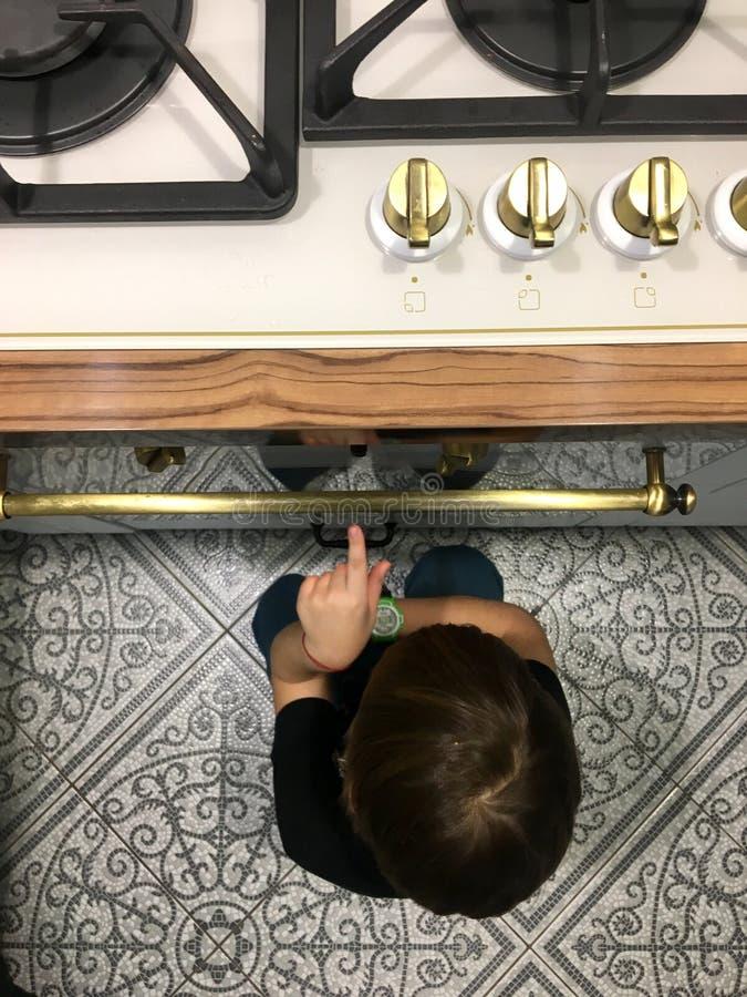 坐在烤箱旁边的一个饥饿的男孩在厨房里 图库摄影