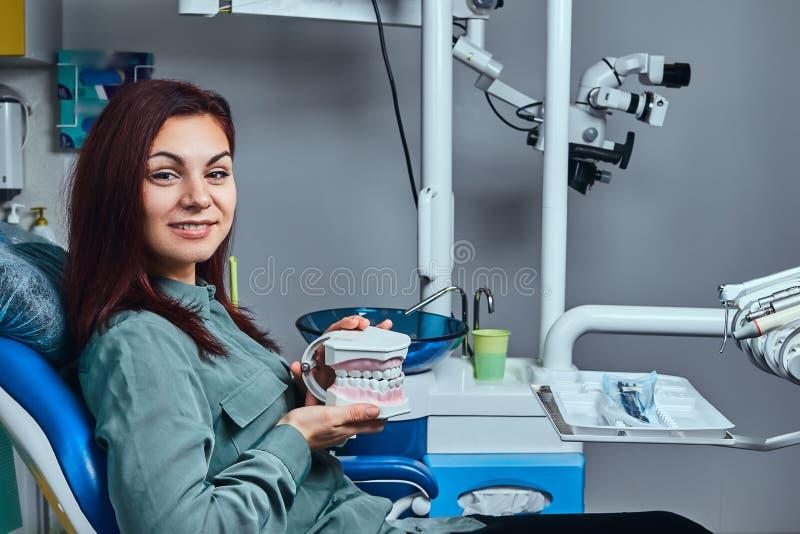 坐在牙医椅子和拿着假牙的年轻红头发人妇女在牙医办公室 免版税库存图片
