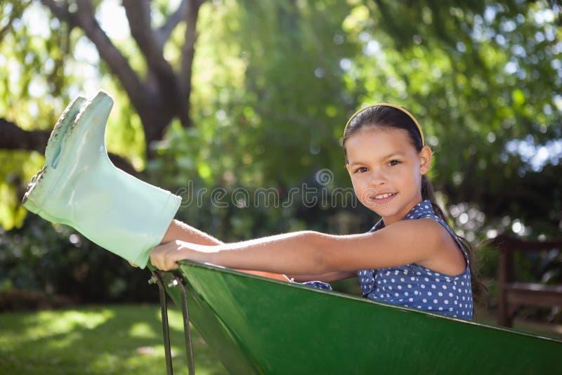 坐在独轮车的女孩画象在后院 免版税库存图片