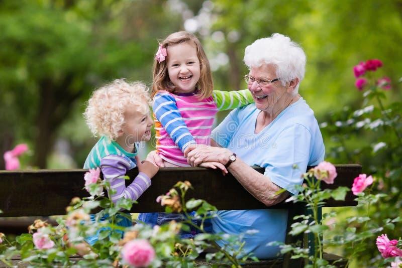 坐在玫瑰园里的祖母和孩子 免版税库存照片