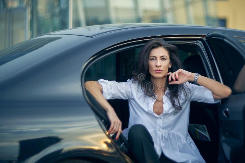 坐在现代办公室门面的汽车的严肃的妇女 免版税库存照片