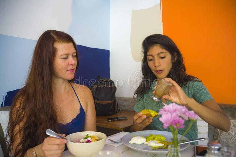 坐在现代咖啡馆的年轻可爱的西班牙女孩生活方式画象吃与企业家妇女的午餐在女朋友 免版税图库摄影
