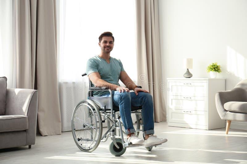 坐在现代轮椅的年轻人 库存照片