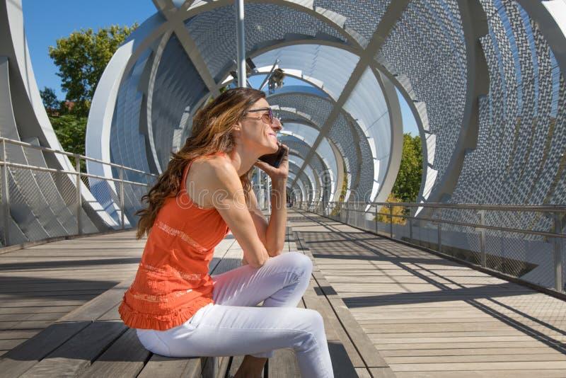 坐在现代都市地方的妇女谈话机动性的 免版税图库摄影
