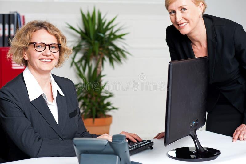 坐在现代办公室的女实业家 免版税库存照片