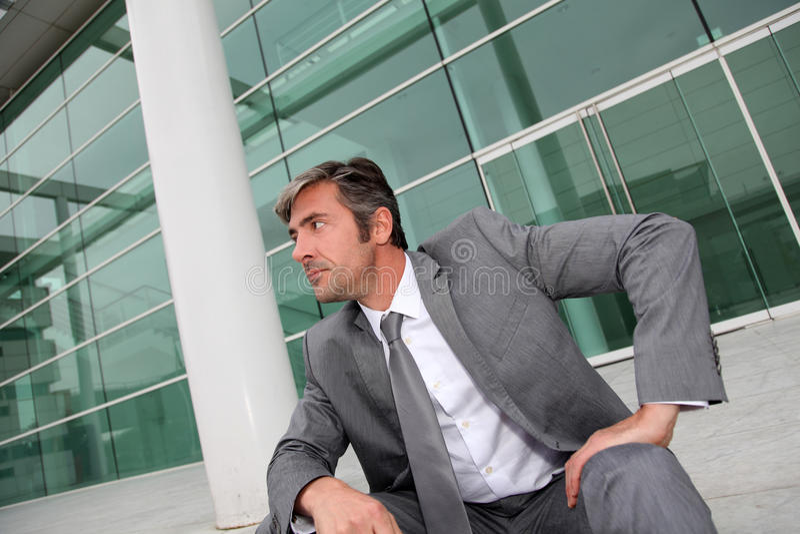 坐在现代大厦前面的商人 免版税库存图片
