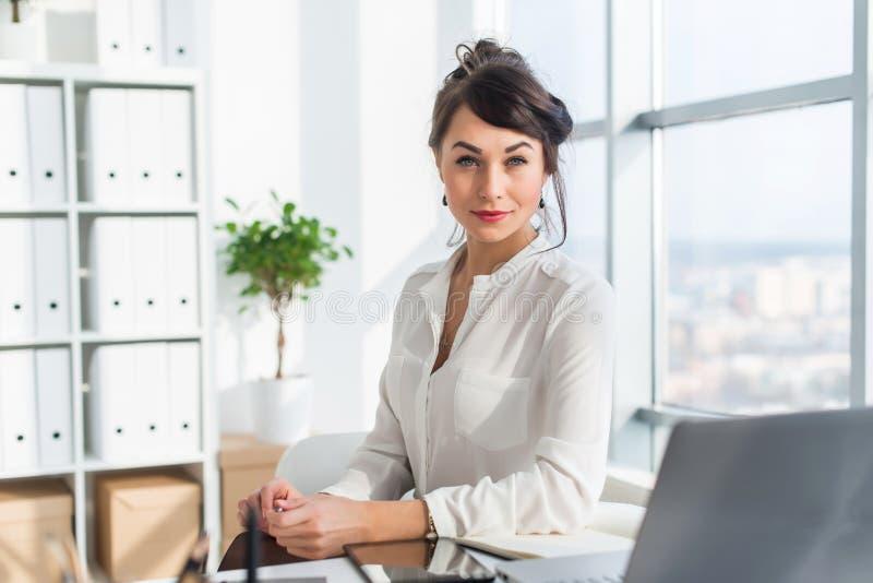 坐在现代顶楼办公室,微笑的妇女的特写镜头画象,看照相机 年轻确信的女性事务 免版税库存图片