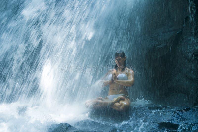 坐在瑜伽姿势的岩石的可爱的妇女精神放松平静和凝思的在惊人的美丽的瀑布和 免版税图库摄影