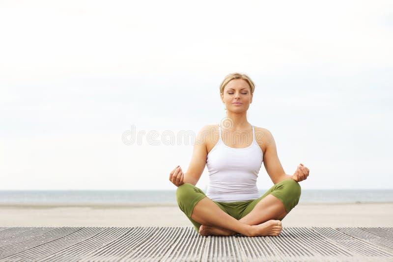 坐在瑜伽姿势的美丽的少妇在海滩 免版税库存图片