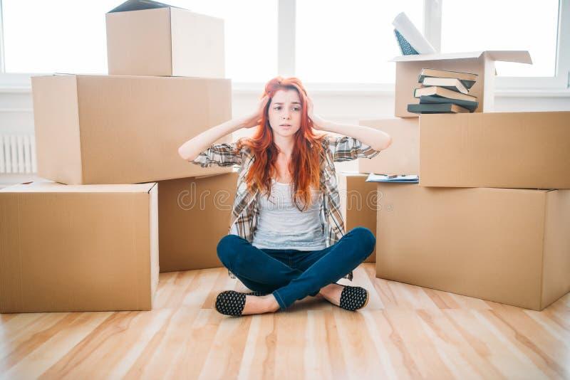 坐在瑜伽姿势,新的家的疲乏的妇女 库存照片